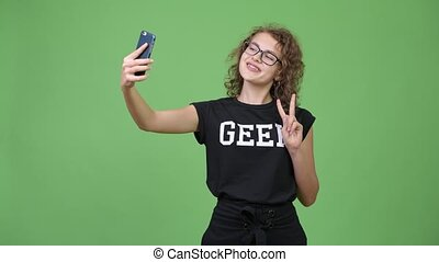 Young happy beautiful nerd woman taking selfie with phone -...