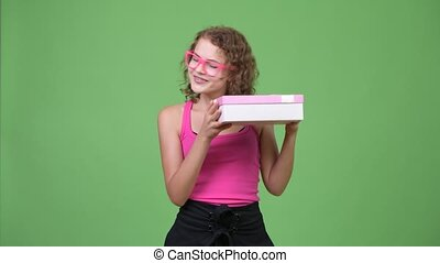 Young happy beautiful nerd woman thinking while holding gift...