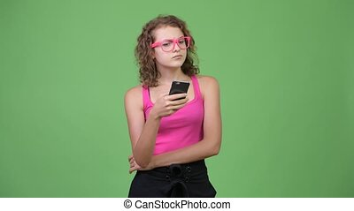 Young happy beautiful nerd woman thinking while using phone...