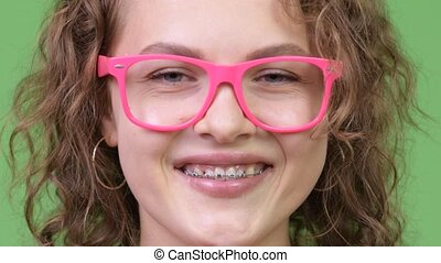 Young happy beautiful nerd woman wearing eyeglasses while smiling with braces