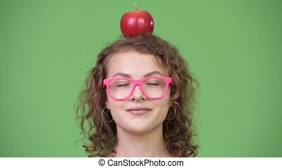 Young happy beautiful nerd woman with red apple on top of...