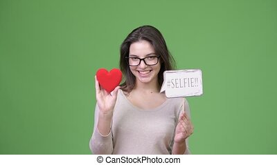 Young happy beautiful woman holding red heart and selfie paper sign