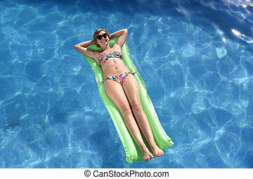 happy beautiful woman in bikini and sunglasses lying relax on float airbed at vacation hotel resort swimming pool