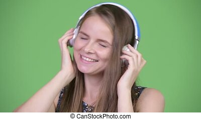 Young happy beautiful woman listening to music