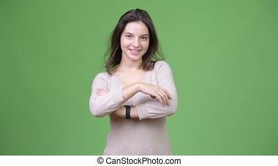 Young happy beautiful woman with arms crossed against green background