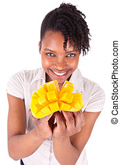 Young happy black / african american woman holding fresh mango