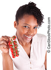 Young happy black / african american woman holding tomatoes