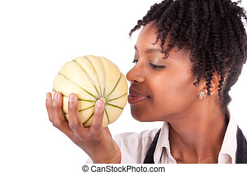 Young happy black / african american woman smelling a fresh melon isolated on white background