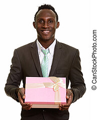 Young happy black African businessman smiling while holding gift