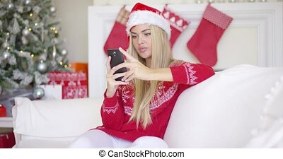 Young happy blond girl in Christmas outfit using mobile phone