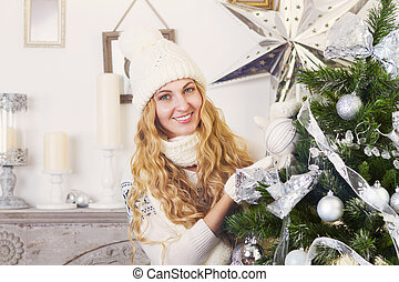 Young happy blond woman near the Christmas tree