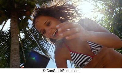 Young happy brunette laughing woman standing near palm tree and making selfie on mobile phone on a blue sky and the sun with lens flare effects background. Girl using smartphone. slow motion.