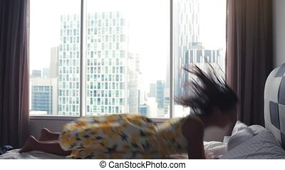 Young happy brunette woman falling down on bed, have fun at careless weekend time. Slow motion.