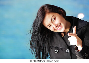 Young happy brunette woman on the beach winking and pointing at you