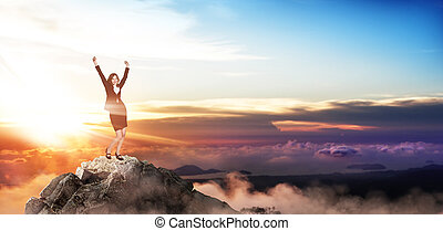 Young happy buiness woman stands on the top of the mountain.
