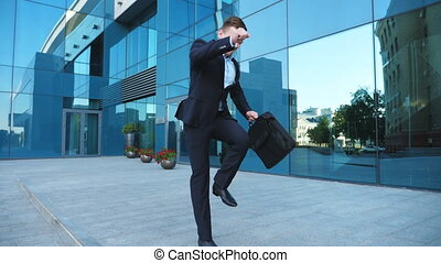 Young happy businessman in suit dances on city street...