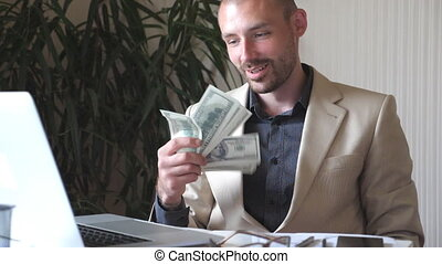 Young happy businessman in suit sitting on his workplace and holding bundle of money in hand. Successful business person rejoices profit. Handsome man smiling and showing joyful emotions. Slow motion