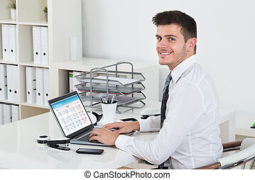 Businessman Looking At The Calendar On Laptop
