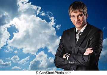 Young happy businessman over cloudy sky