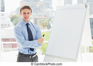 Young happy businessman standing by whiteboard