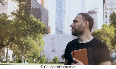 Young happy businessman with documents standing in the park, near the financial district in New York, America.