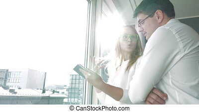 Young happy businesspeople with pad by the window - Young...