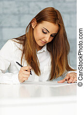 Young happy businesswoman signing document