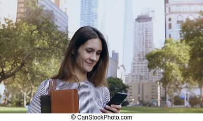 Young happy businesswoman standing in financial district of...