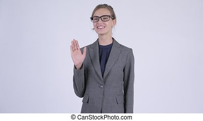 Young happy businesswoman with eyeglasses waving hand -...