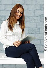 Young happy businesswoman with tablet computer in office