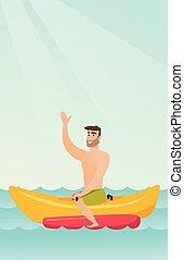 Young happy caucasian man riding a banana boat.