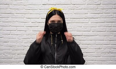 Young happy Caucasian woman in black jacket takes off protective medical mask from coronavirus and smiling with teeth on white brick wall background close up. Covid 19 virus recovery concept.
