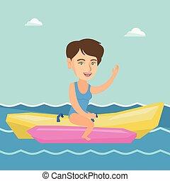 Young happy caucasian woman riding a banana boat.