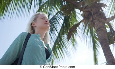 Young happy caucasian woman with long blonde hair in sunglasses and green shirt stand with closed eyes and smiling near palm tree on a blue sky background. Travel concept