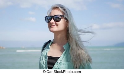 Young happy caucasian woman with long blonde hair in sunglasses and green shirt standing and smiling near palm tree on a blue sea background. Travel concept