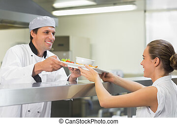 Young happy chef handing a plate to the waitress