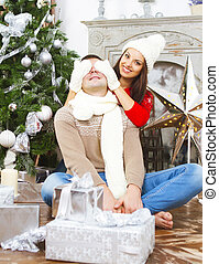 Young happy couple by the Christmas tree