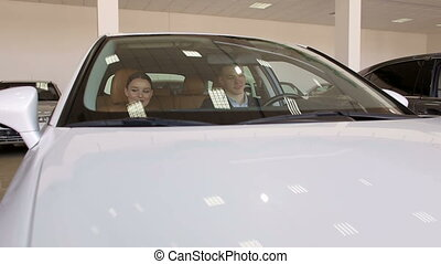 Young couple watching a new white car in the showroom of the dealership.