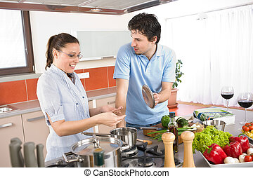 Young happy couple cooking in kitchen