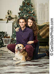 Young happy couple cuddling with a dog sitting on the floor near the Christmas tree