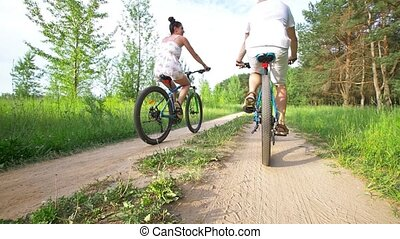 Young happy couple cycling on the path in summer field