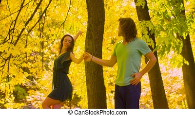 Young happy couple dancing in the autumn park
