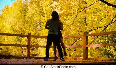 Young happy couple dancing on the bridge