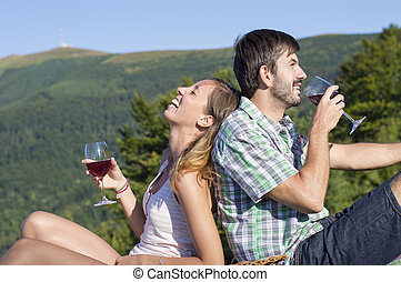 Young happy couple drinking wine on a hiking trip at the viewpoint