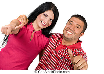 Young happy couple embrace with thumbs-up