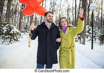 young happy couple enjoy walking on winter street with red air balloons