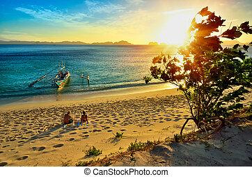 Young happy couple enjoying a beautiful sunset on the beach island of El Nido