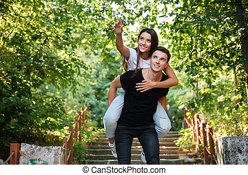 Young happy couple enjoying piggyback ride at the park