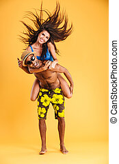 Young happy couple enjoying piggyback ride