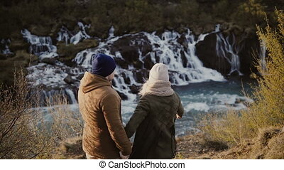 Young happy couple exploring the mountains valley and waterfalls in Iceland. Woman showing something to man.